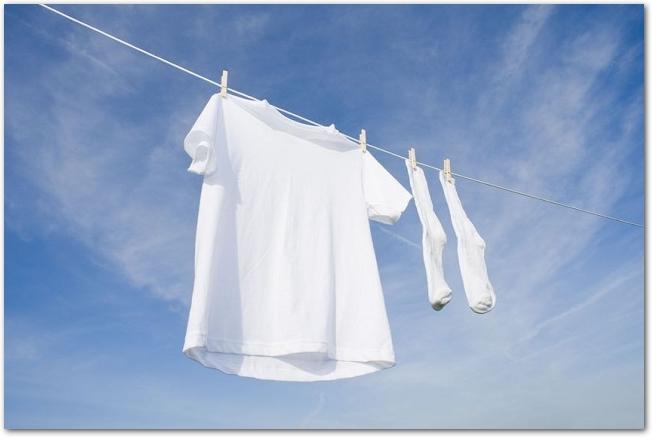 青空の下に干してある白いシャツと靴下