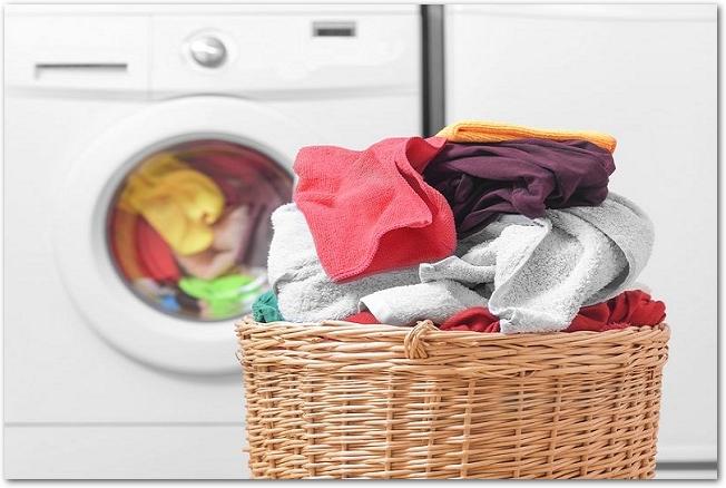 洗濯機とその前に置かれた洗濯物の入ったカゴ