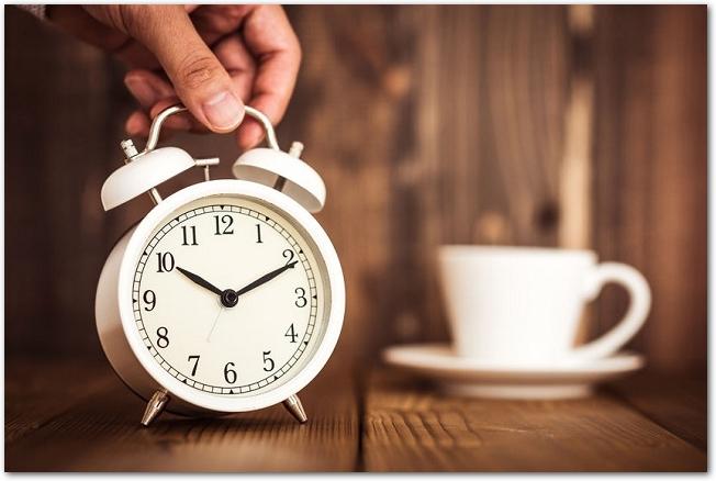 木のテーブルに白いレトロな時計を置いている手の様子