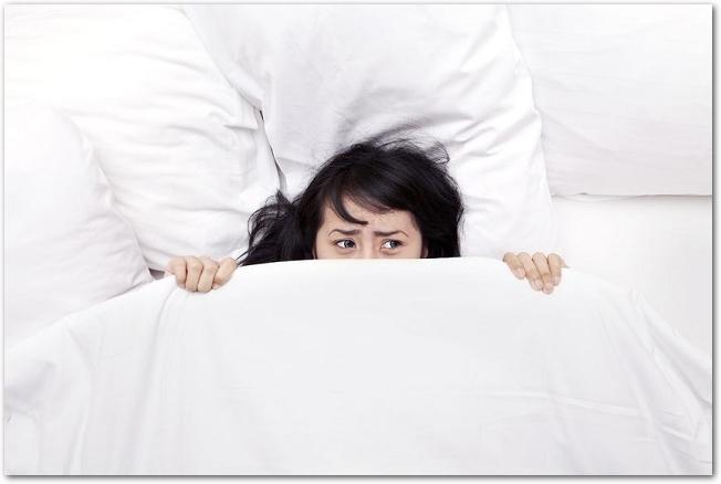 眠れずに鼻から上だけを布団から出しているしかめっ面の女性の様子