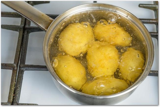 皮つきのじゃがいもを鍋で茹でている様子