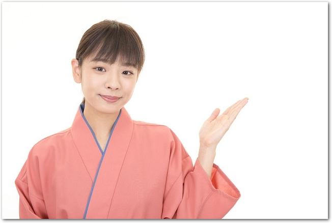 左手で指し示す着物姿の女性