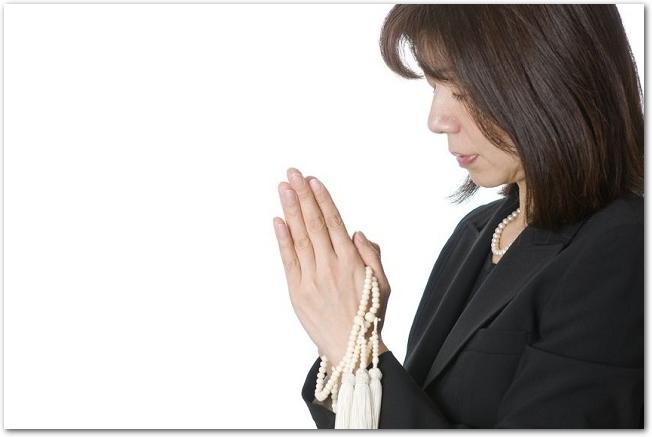 手に数珠をかけて拝む喪服の女性の様子