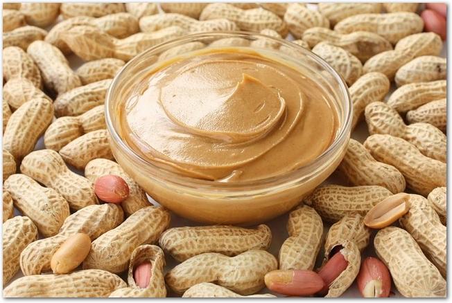 殻付きのピーナッツの上にガラス容器に入ったピーナッツバターが置かれている様子
