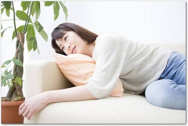 ソファーに横になる疲れた表情の女性の様子