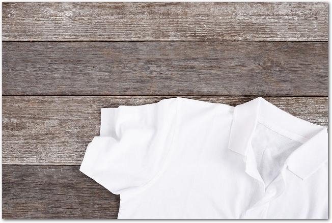 木製のテーブルに置かれた白いポロシャツ