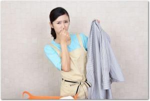洗濯物を持ち鼻をつまむエプロン姿の女性の様子