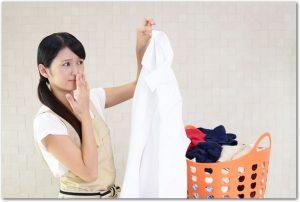 洗濯物の白シャツをつまんで鼻を押さえる主婦の様子