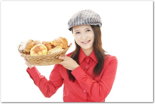 バスケットに入った色々なパンを持つパン屋の女性店員