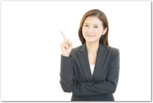 指を指して注意をうながすスーツ姿の女性の様子