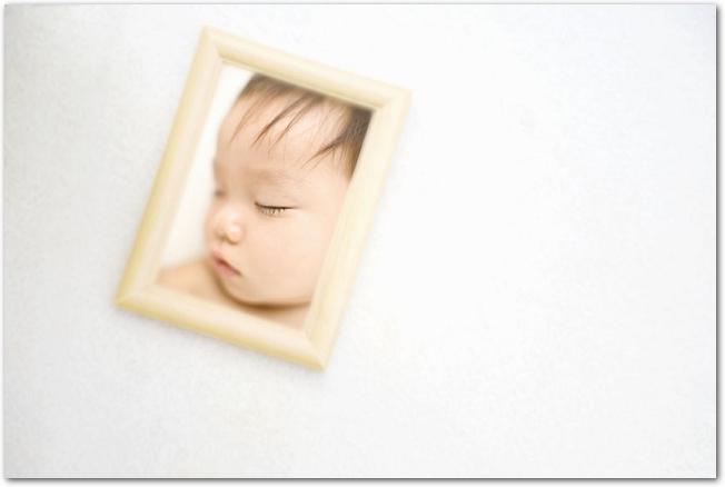 白い背景に置かれた木のフレームに入った赤ちゃんの写真