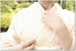 淡い無地の着物を着た女性が襟元に手をやっている様子