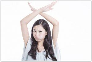 両手でバツ印を作る起こった表情の女性