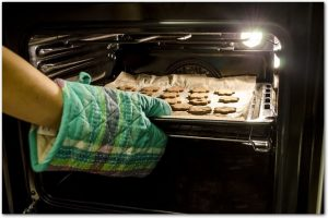 天板に並べたクッキー生地をオーブンに入れている様子