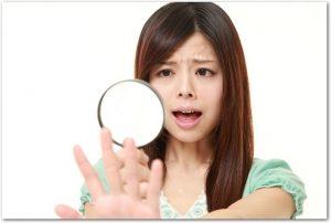 自分の爪を拡大鏡で見てショックを受けている女性の様子
