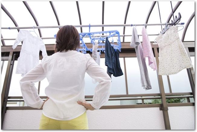 ベランダに干した洗濯物を眺める女性の後ろ姿