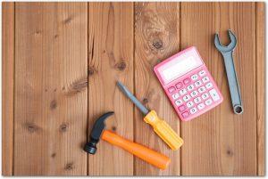 大工道具と電卓が木の床に置いてある様子