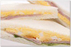 卵やハムなどの具材が入ったサンドイッチの断面