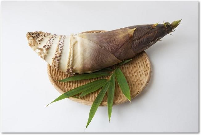 木のザルに乗った皮つきのたけのこと笹の葉