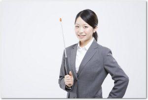 指し棒を持つスーツ姿の女性の様子