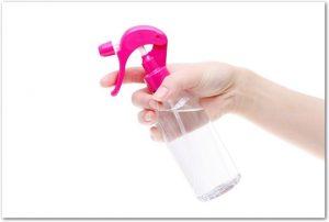 ピンクのキャップのスプレーボトルを持つ右手の様子