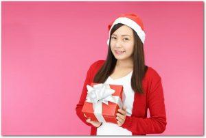 サンタ帽をかぶった笑顔の女性がプレゼントを持っている様子