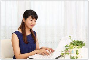 自宅のノートパソコンでネットショッピングをする女性の様子