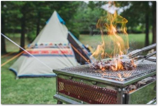 キャンプ場のテントの手前で肉を焼いている様子