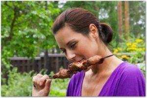 バーベキューのお肉を食べている女性の様子